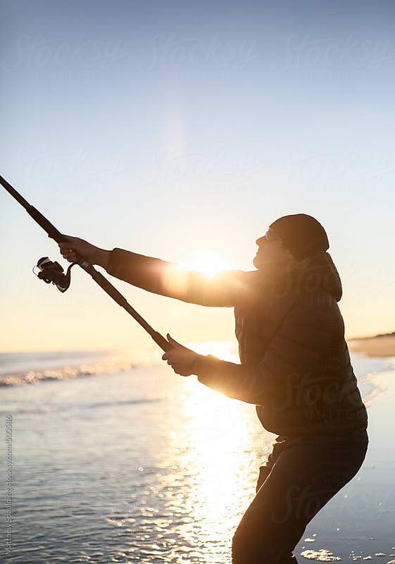 Person casting fishing pole to catch surf fish on atlantic ocean beach by Matthew Spaulding for Stocksy United