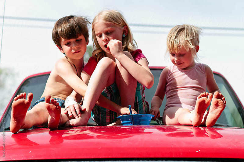 three children sitting on hood of truck  by Jess Lewis for Stocksy United