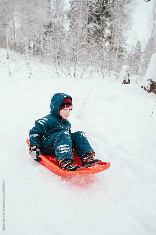 Boy Riding Sled Down Hill by Stephen Morris for Stocksy United