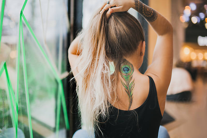 Girl with a peacock feather tattoo by Irina Efremova for Stocksy United