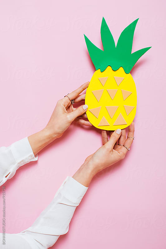 Woman hands holding cardboard pineapple in front a pink background. by BONNINSTUDIO for Stocksy United