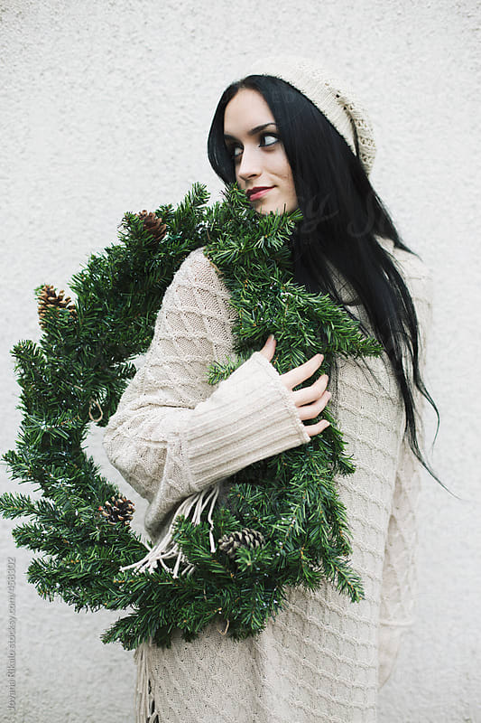 Young woman carrying a Christmas wreath by Jovana Rikalo for Stocksy United
