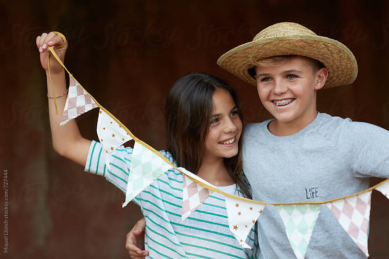 Brother and sister celebrating a party with decoration flags by Miquel Llonch for Stocksy United