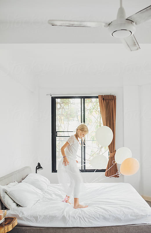Girl Playing With Balloons in the Bedroom by Lumina for Stocksy United