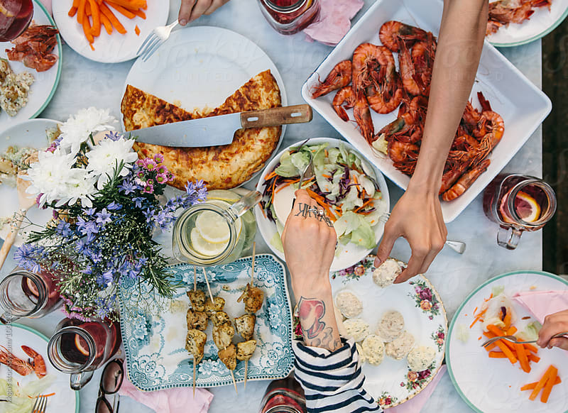 Overhead view of a table full of food with hands by kkgas for Stocksy United