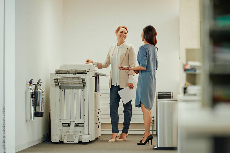 Two young business women interacting next to office photocopier by Aila Images for Stocksy United