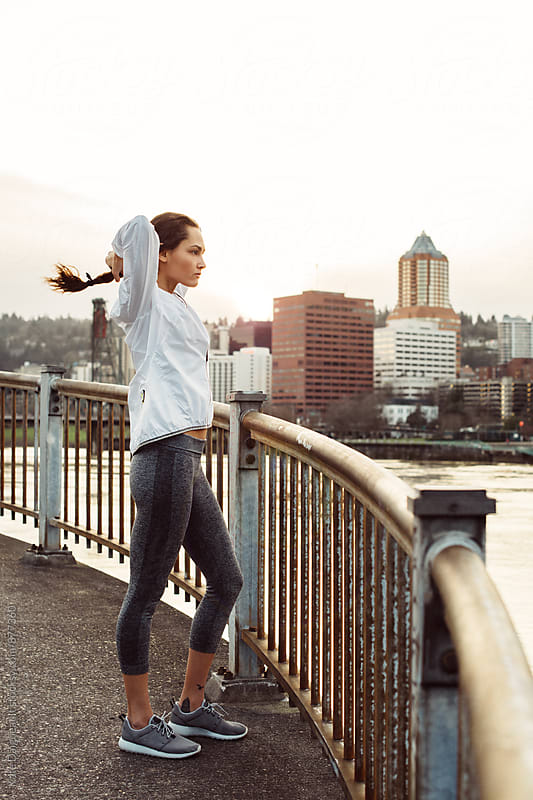 Fit young woman exercising by the city waterfront at dusk by Kate Daigneault for Stocksy United