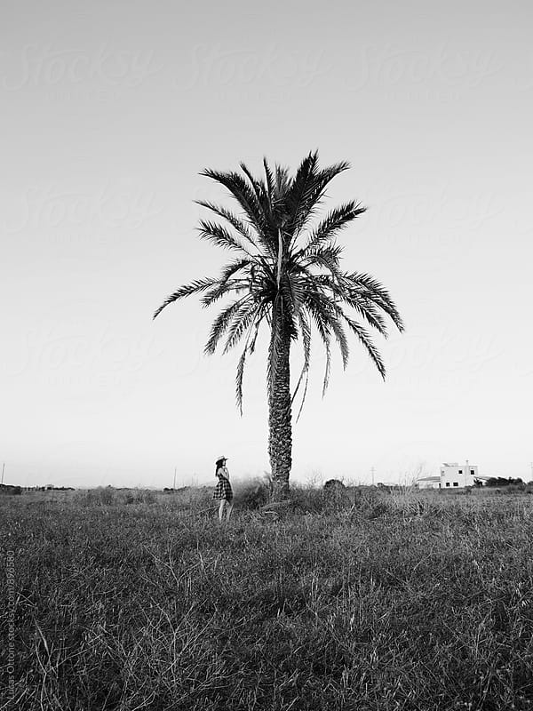 In black and white: girl under a Palm Tree by Lucas Ottone for Stocksy United