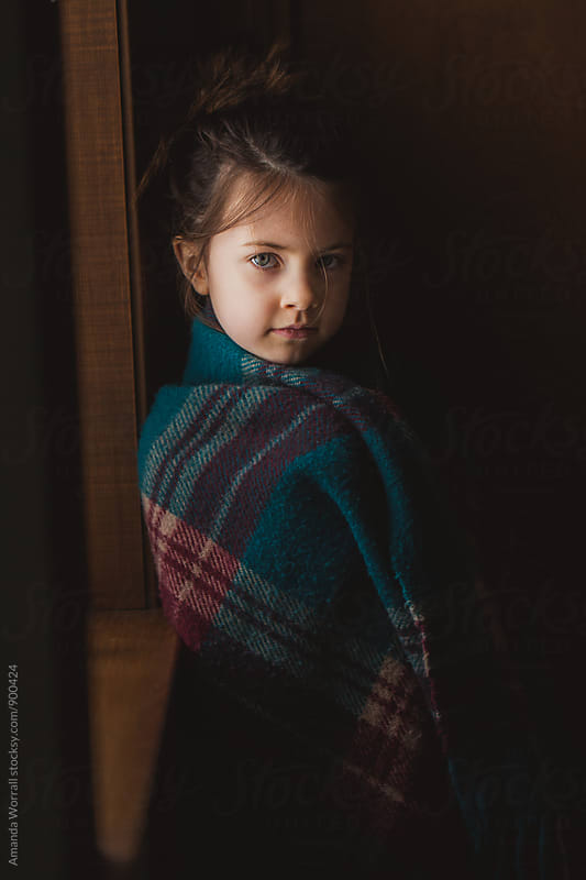 Portrait of young girl wrapped in a plaid blanket, looking at camera by Amanda Worrall for Stocksy United