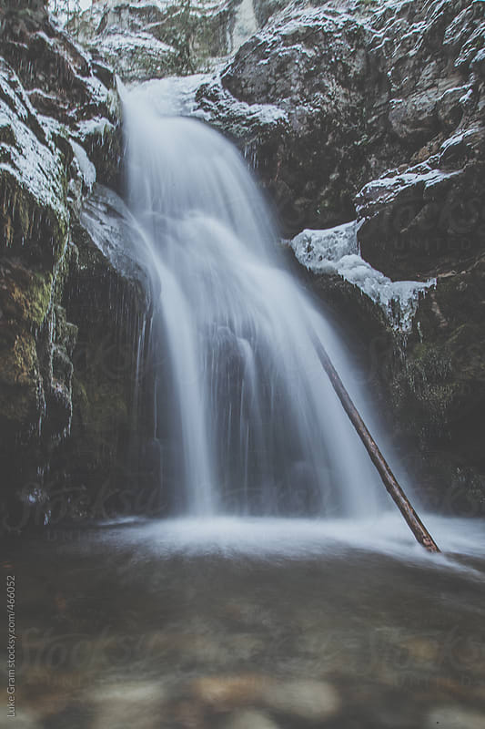 Waterfall flowing into river from a canyon by Luke Gram for Stocksy United