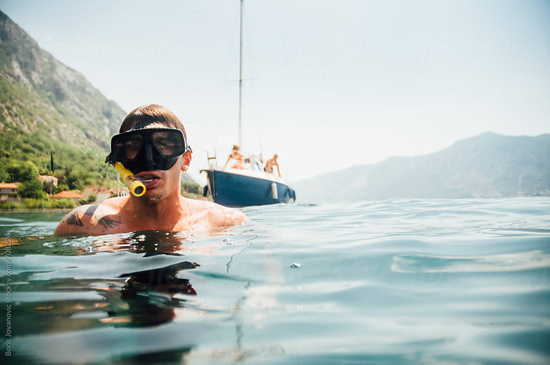 Breath hold diver floating in front of his boat by Boris Jovanovic for Stocksy United
