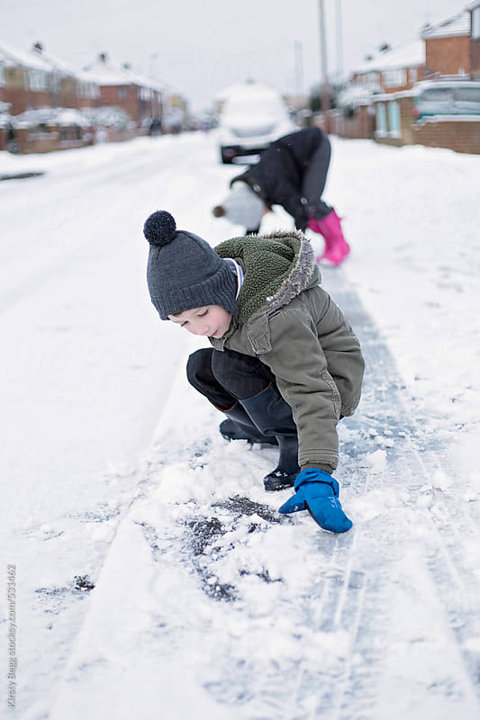 Children playing in snowy street by Kirsty Begg for Stocksy United