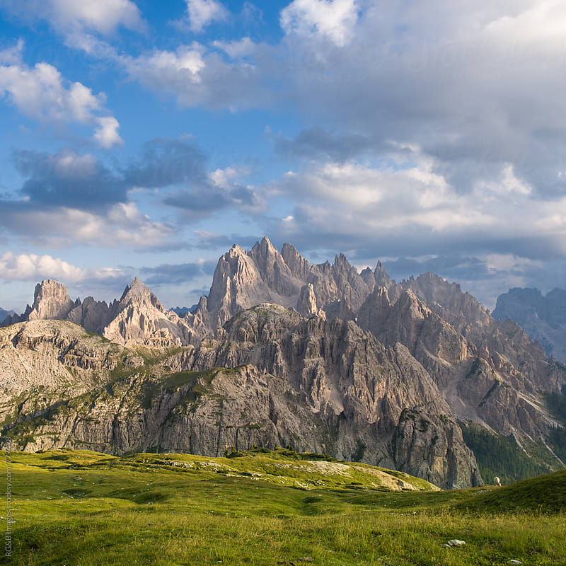 Rocky mountain peaks and green meadow in the Alps by RG&B Images for Stocksy United