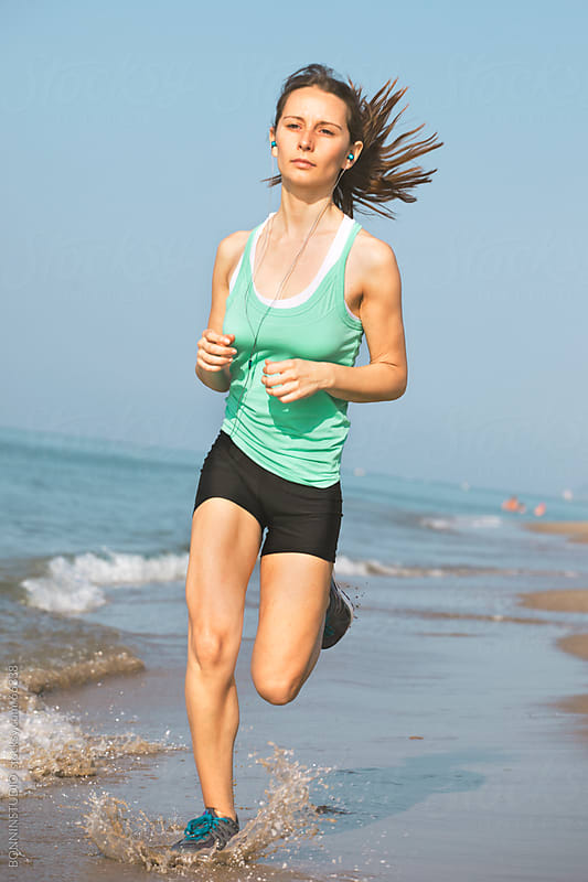 Beautiful young athletic woman running  on the beach. She is listening music. by BONNINSTUDIO for Stocksy United