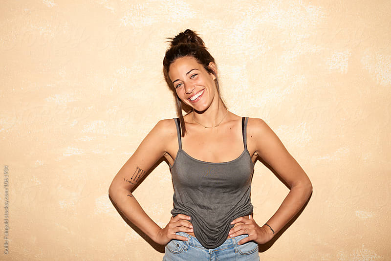 Young cheerful brunette smiling at camera with hands on waist by Guille Faingold for Stocksy United