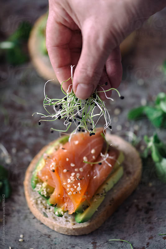 Woman placing sprouts on salmon sandwich by Pixel Stories for Stocksy United