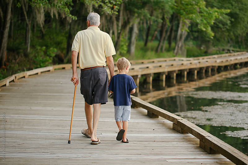 boy and his grandfather take a walk by Kelly Knox for Stocksy United