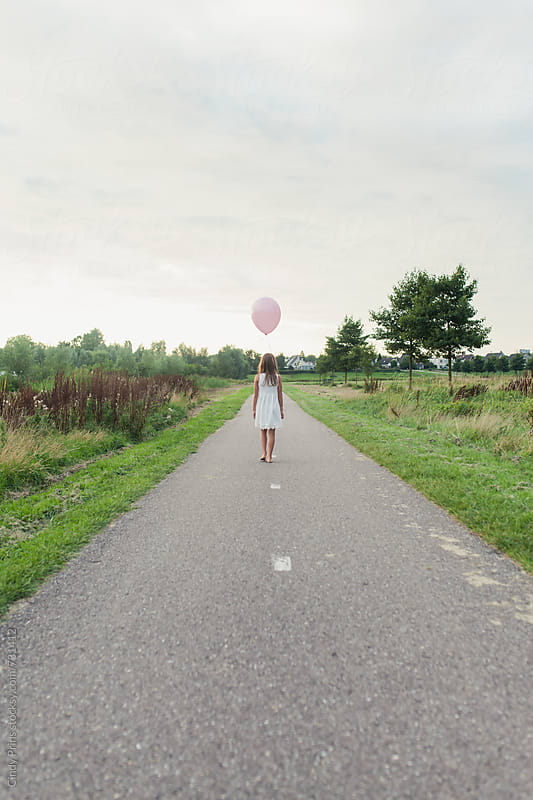 Back view of a little girl with pink balloon walking on a long road by Cindy Prins for Stocksy United