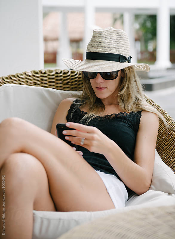 Woman looks down at her smart phone while on vacation by Emmanuel Hidalgo for Stocksy United