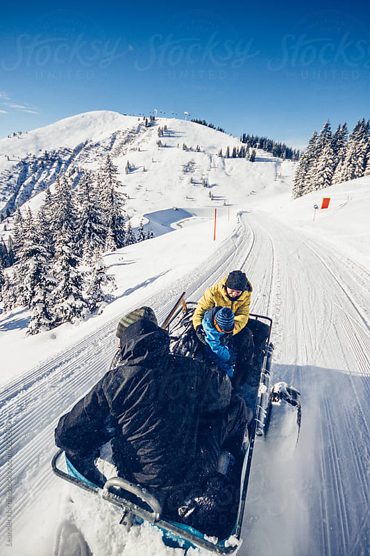 young family taking a ride on the back of a snowmobile through austrian skiing area by Leander Nardin for Stocksy United