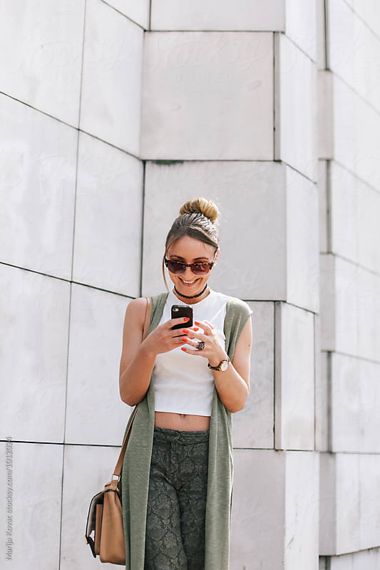 Happy woman smiling and looking at her mobile phone by Marija Kovac for Stocksy United