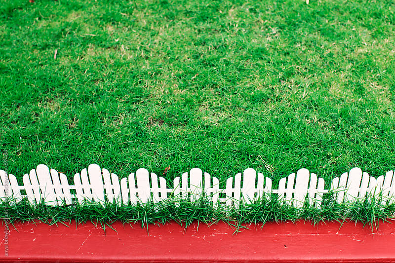 Image of a green lawn with white picket fencing and red pavement by anya brewley schultheiss for Stocksy United