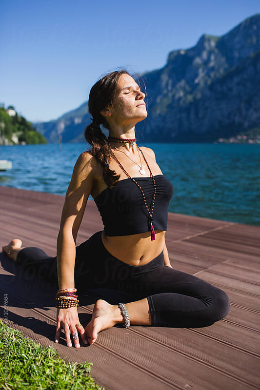 Woman doing yoga by the lake by michela ravasio for Stocksy United