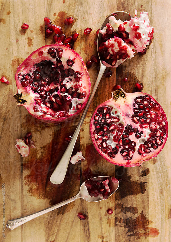 Pomegranate Cut Open on Cutting Board by Jeff Wasserman for Stocksy United