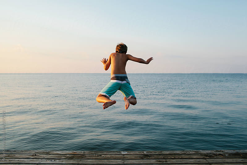 boy jumping off of a pier into a lake at sunset by Kelly Knox for Stocksy United