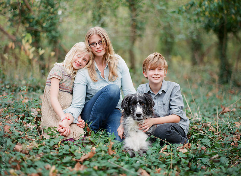 Family of three sitting in the ivy woods with their pet dog by Marta Locklear for Stocksy United