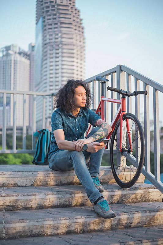 Young Asian man sitting next to his bike by Jovo Jovanovic for Stocksy United