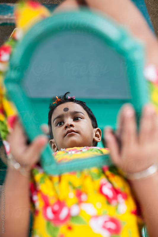A little Indian Girl with reflection at mirror by PARTHA PAL for Stocksy United
