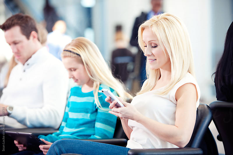 Airport: Mother Using a Smart Phone While Waiting for Flight by Sean Locke for Stocksy United