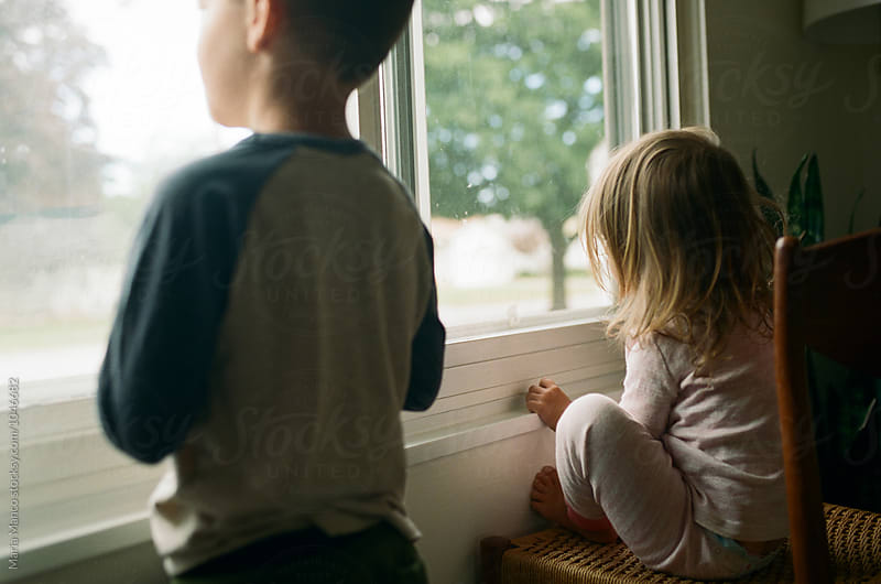 kids looking out window by Maria Manco for Stocksy United