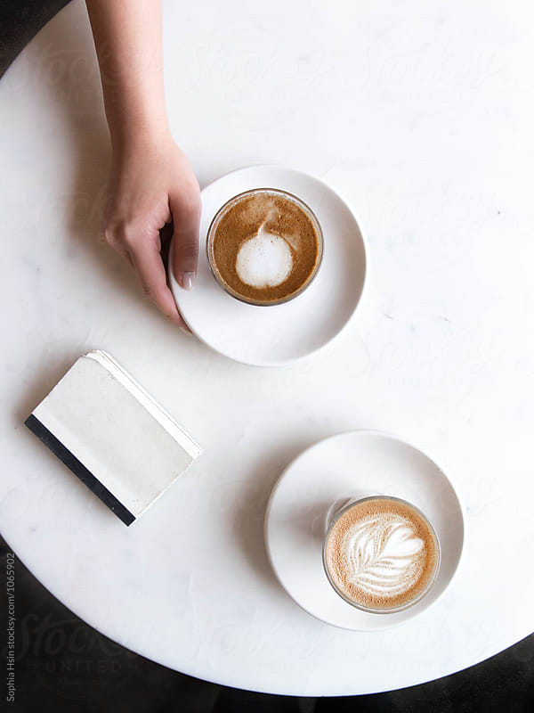 Hand holding coffee on marble table by Sophia Hsin for Stocksy United