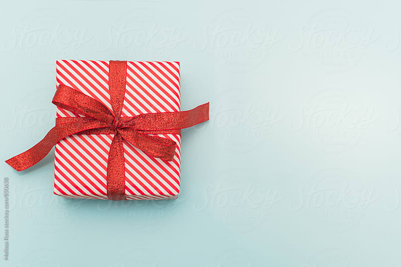 Small red and white wrapped gift on blue - wide by Melissa Ross for Stocksy United