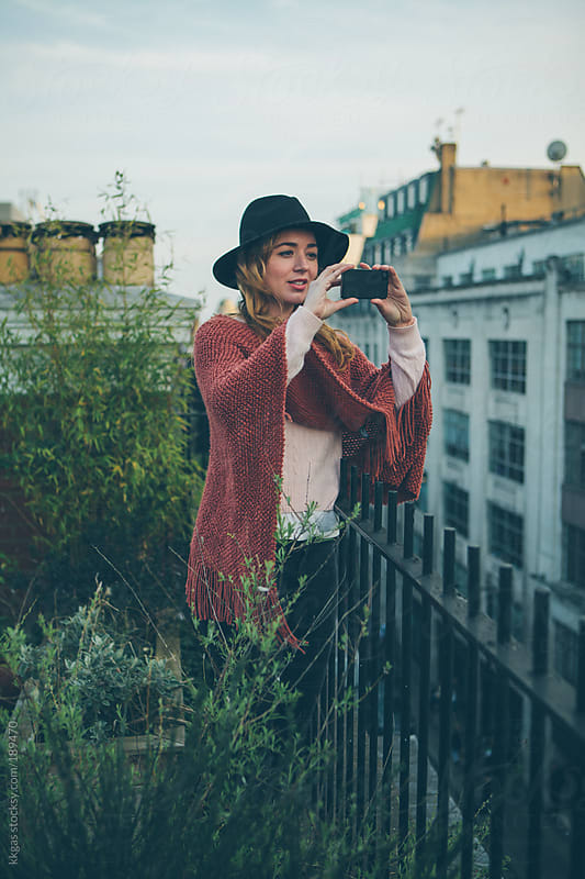 Blonde woman on a roof taking a picture with phone  by kkgas for Stocksy United