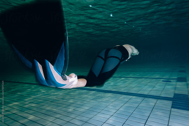 Free diver swimming with monofin in the pool underwater by Jovana Milanko for Stocksy United