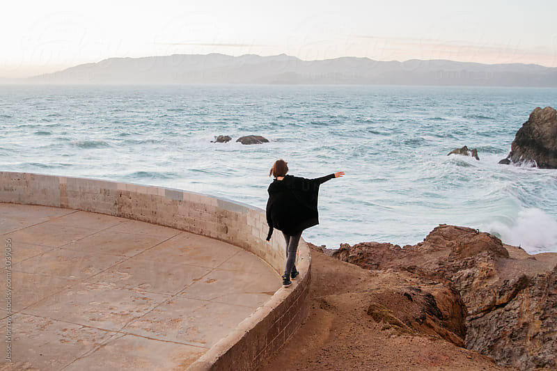 young female woman walks along railing at sunset near ocean coast by Jesse Morrow for Stocksy United