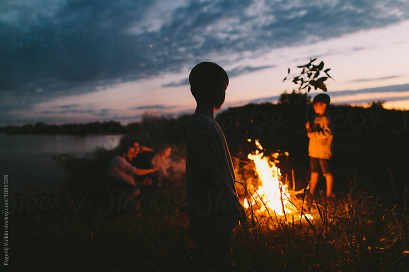 Parents and their three boys looking at the night fire  by Evgenij Yulkin for Stocksy United