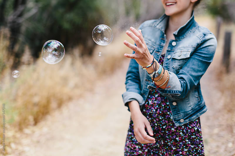 Teen girl laughing and playing with bubbles in the bush by Jacqui Miller for Stocksy United
