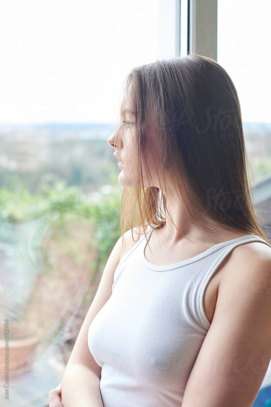 Woman looking through the window by Jose Coello for Stocksy United