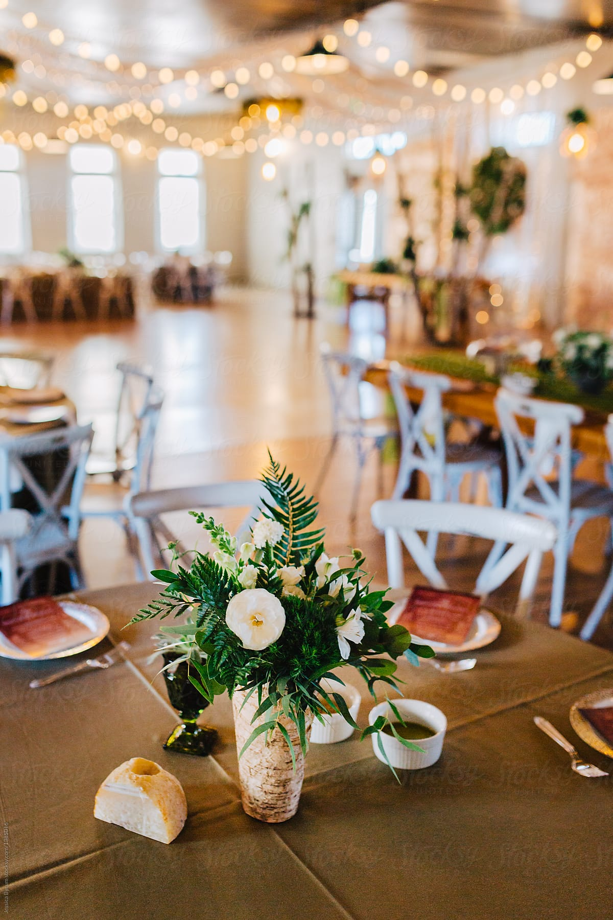 A venue set up for a wedding reception with copper and green colored decor.  by Jessica Byrum - Reception, Flower - Stocksy United