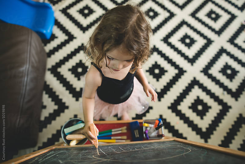 Child drawing on chalkboard from above  by Courtney Rust for Stocksy United