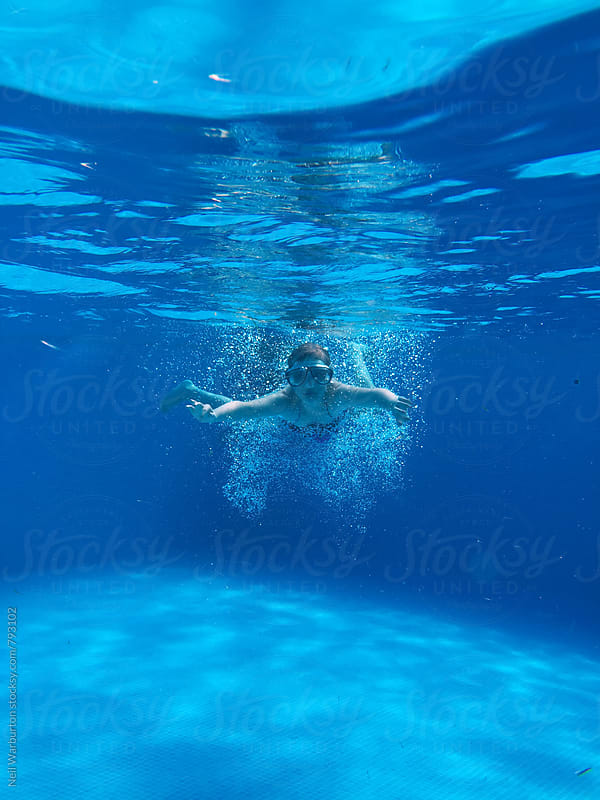 Teenage girl swimming in an outdoor pool by Neil Warburton for Stocksy United