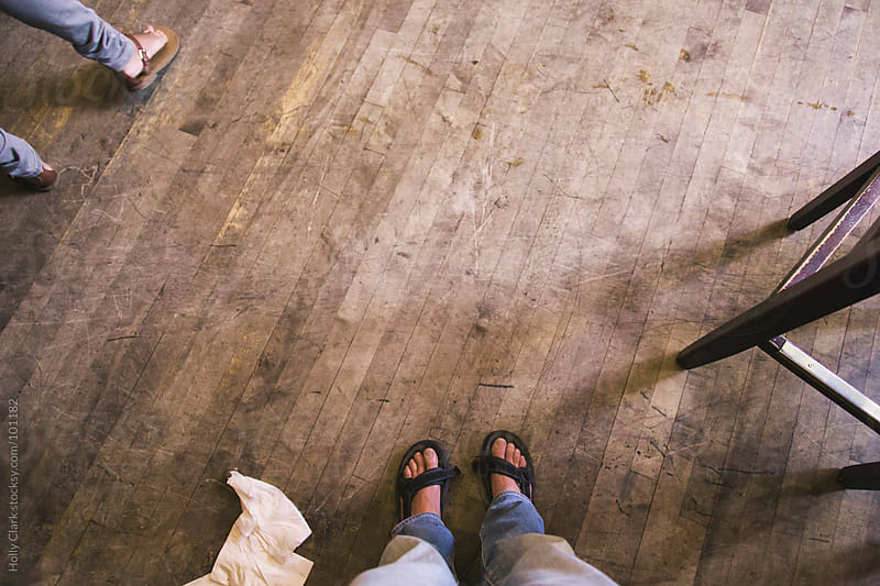 Lookin down on feet standing on a dirty, scarred wooden floor. by Holly Clark for Stocksy United