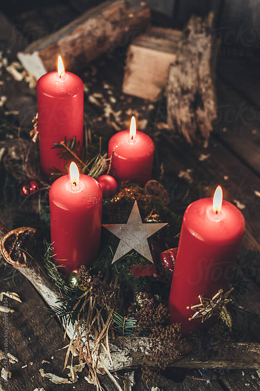 advent wreath with four red burning candles on rustic background by Leander Nardin for Stocksy United