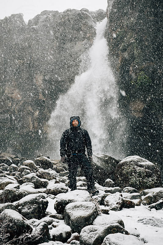 hiker standing at snowy waterfall by Cameron Zegers for Stocksy United