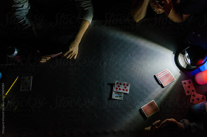 overhead late-night card game by Margaret Vincent for Stocksy United