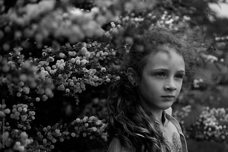 Moody portrait of a young girl amongst blossoms by skye torossian for Stocksy United